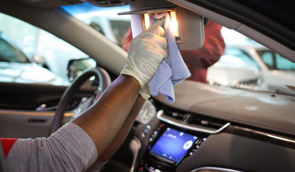 Человек протирает зеркало в автомобиле