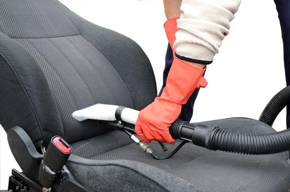 Человек пылесосит автомобильное сидение