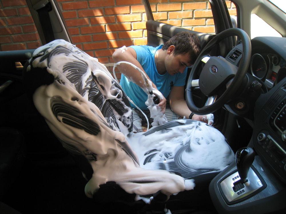 Парень делает химчистку сидений в автомобиле