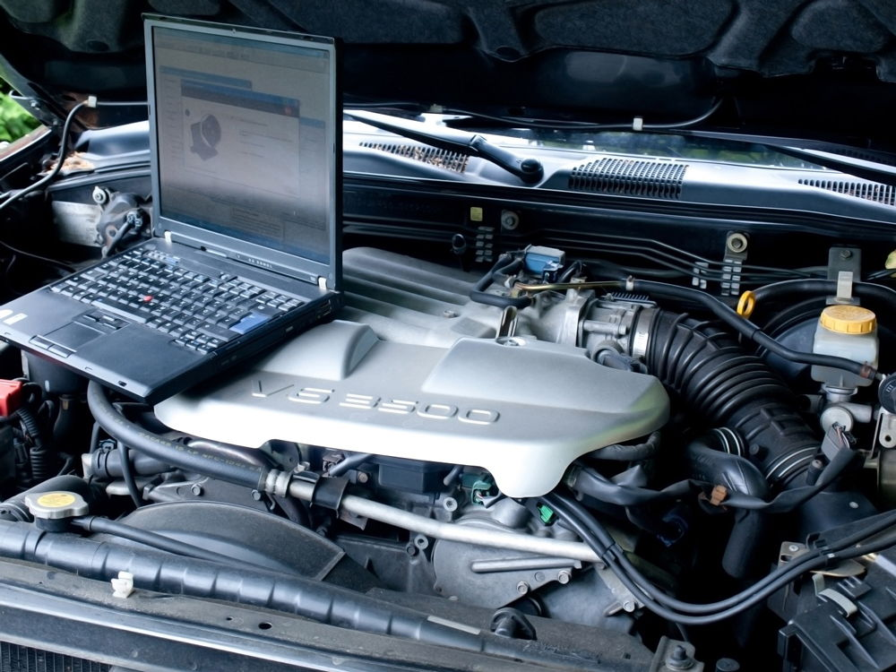 Ноутбук лежит на двигателе автомобиля