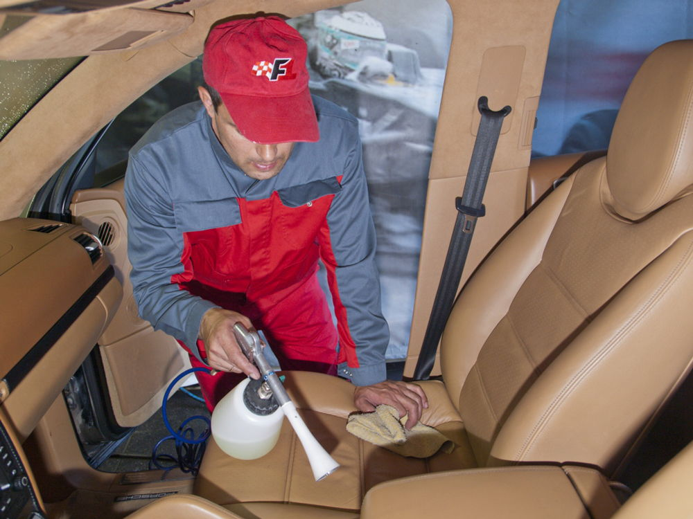 Парень чистит салон автомобиля