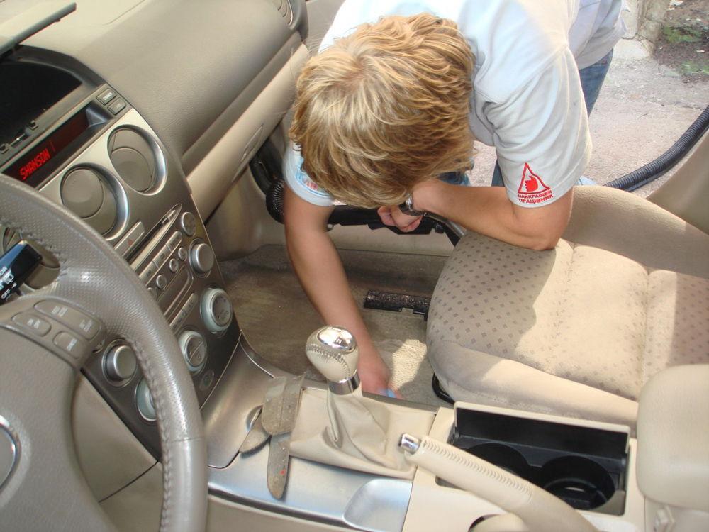 Парень чистит пол автомобиля