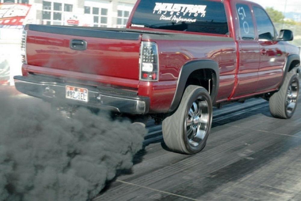 У красного пикапа идет дым с выхлопной трубы