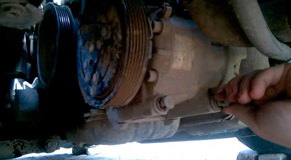 Откручивание болтов крепления компрессора автокондиционера